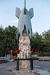 Цветы и свечи у памятника мирным жителям